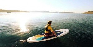 kneeling on a stand up paddle board